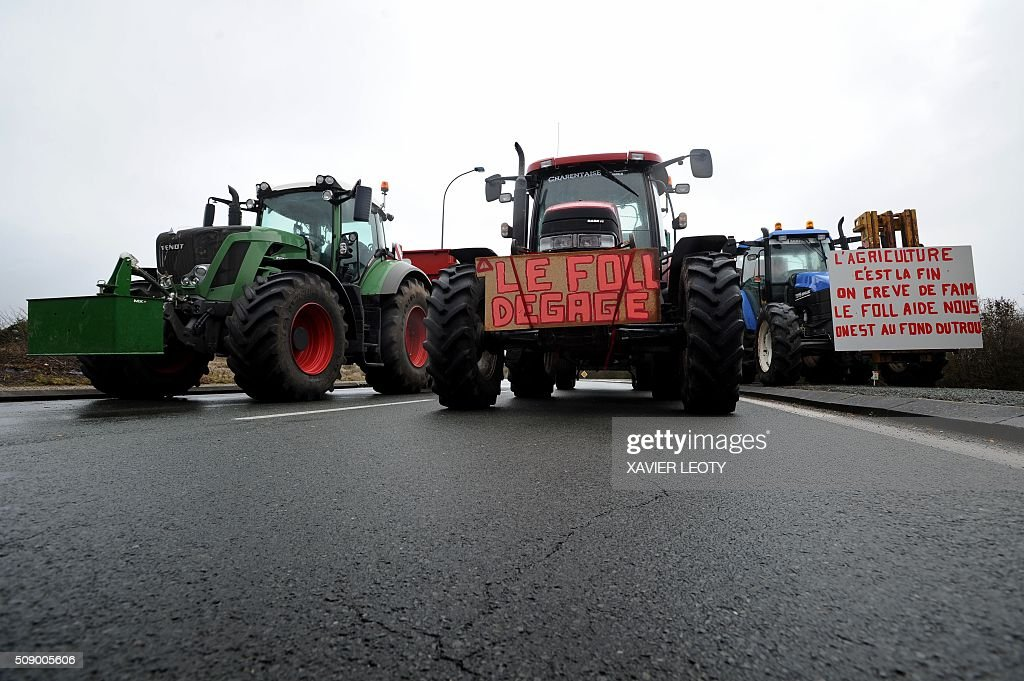 French farmers stand next to tractors as they block a road near Saintes on February 08, 2016 to protest against the falling prices of their products.About 300 farmers, mostly pig and dairy farmers, paralyzed the city of Saintes with the help of about 150 tractors. / AFP / XAVIER LEOTY / AFP / XAVIER LEOTY