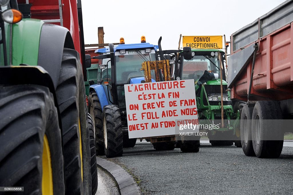 A protester walks past tractors and shopping trolleys as he and others block a road near Saintes, western France, on February 8, 2016, during a demonstration by farmers against the purchase price of their products by supermarkets. Over 100 tractors were used by mostly pig and dairy farmers to block strategic points giving access to the city, disrupting traffic and closing an interchange of the A10 motorway. / AFP / XAVIER LEOTY