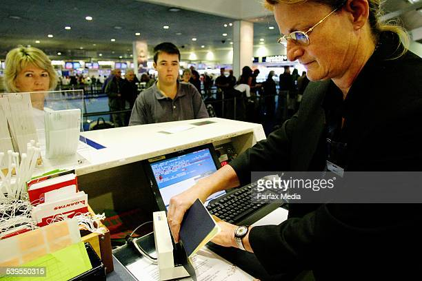 Picture shows Qantas worker Melanie Kasteleiner swiping the passport of Jeremy Brown at the checkin desk 24 April 2004 SHD Picture by JANE DYSON