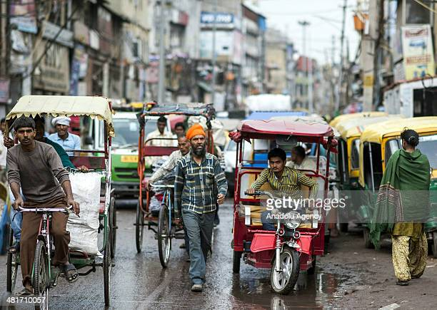 Picture shows rickshawriders on the busy streets of New Delhi's Shahjahanabad the walled old city part of India's capital on March 31 2014 With its...