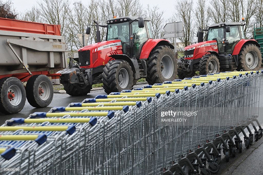 A picture shows shopping trolleys and tractors as protesters block a road near Saintes, western France, on February 8, 2016, during a demonstration by farmers against the purchase price of their products by supermarkets. Over 100 tractors were used by mostly pig and dairy farmers to block strategic points giving access to the city, disrupting traffic and closing an interchange of the A10 motorway. / AFP / XAVIER LEOTY