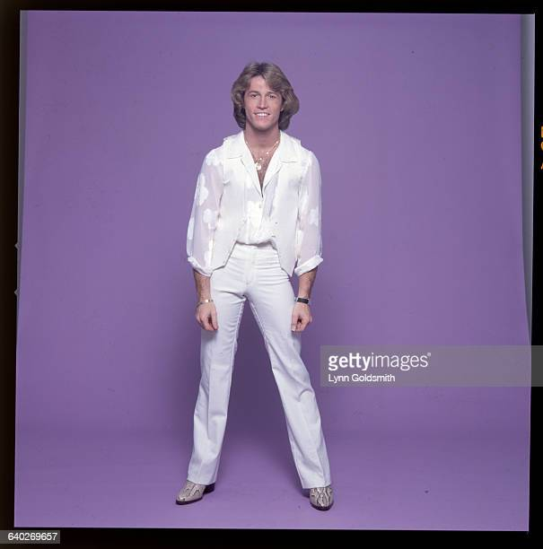 1980 Picture shows singer Andy Gibb posing in tight white pants and a white shirt and vest He is wearing a gold chain and smiling and shown in front...