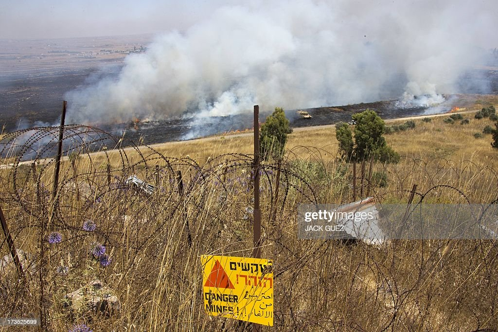 A picture shows smoke billowing after mortar fire from inside war-torn Syria hit the Israeli-occupied Golan Heights on July 16, 2013 causing several wildfires to break out along the ceasefire line. The apparently stray rounds struck as Syrian rebels and regime forces battled near Quneitra which lies in no-man's land, the correspondent reported. Israel, which remains technically at war with Syria, seized 1,200 square kilometres (460 square miles) of the strategic plateau during the 1967 Six-Day War, which it later annexed in a move never recognised by the international community. AFP PHOTO / JACK GUEZ