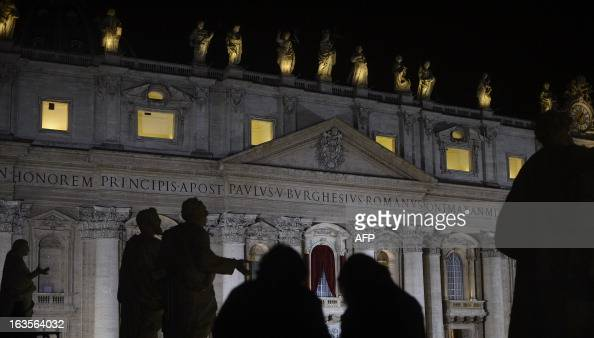 A picture shows St Peter's basilica at night and the balcony where the new pope will appear after the conclave on March 12 2013 at the Vatican...