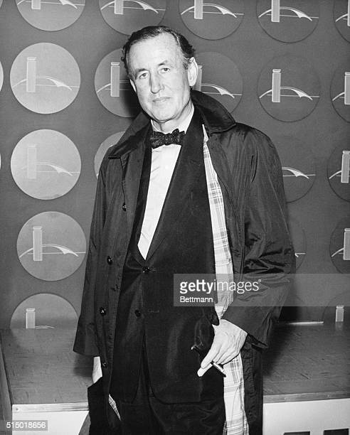 1962 Picture shows the author of the James Bond series Ian Fleming posing in a tuxedo and over coat and smoking a cigarette
