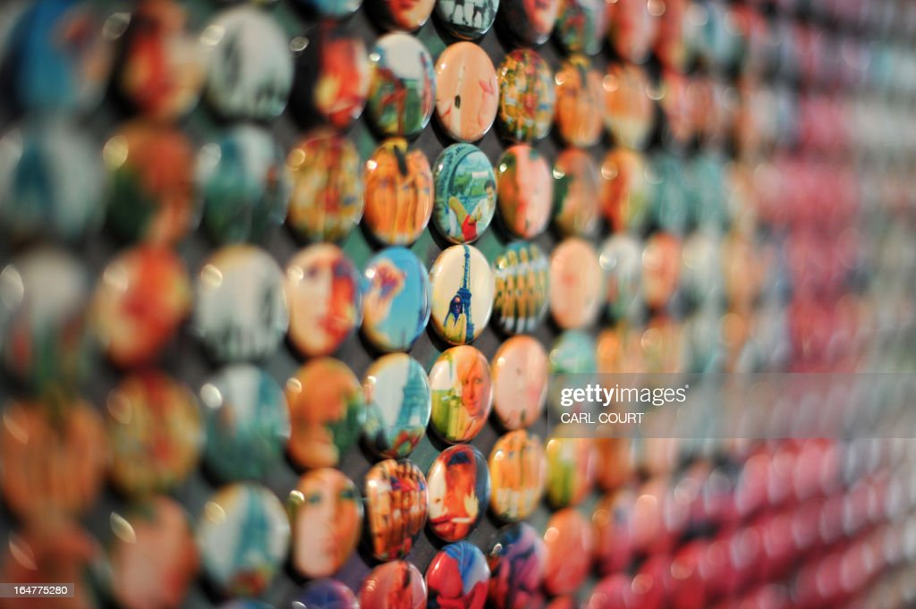 A picture shows the badges that form an art work depicting French former IMF chief Dominique Strauss-Kahn entitled 'La Pig' by British artist Joe Black at the Opera Gallery in central London on March 28, 2013. The work is made up of small badges showing pornographic images and photos of piglets and was created for French magazine Paris Match to celebrate its publication of 1001 covers since 1949.