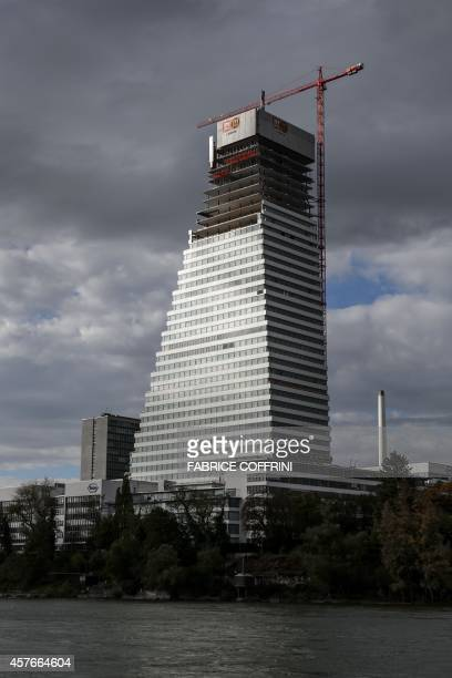 A picture shows the Building 1 tower of Swiss pharmaceutical giant Roche under construction on the banks of the Rhine river in Basel on October 22...