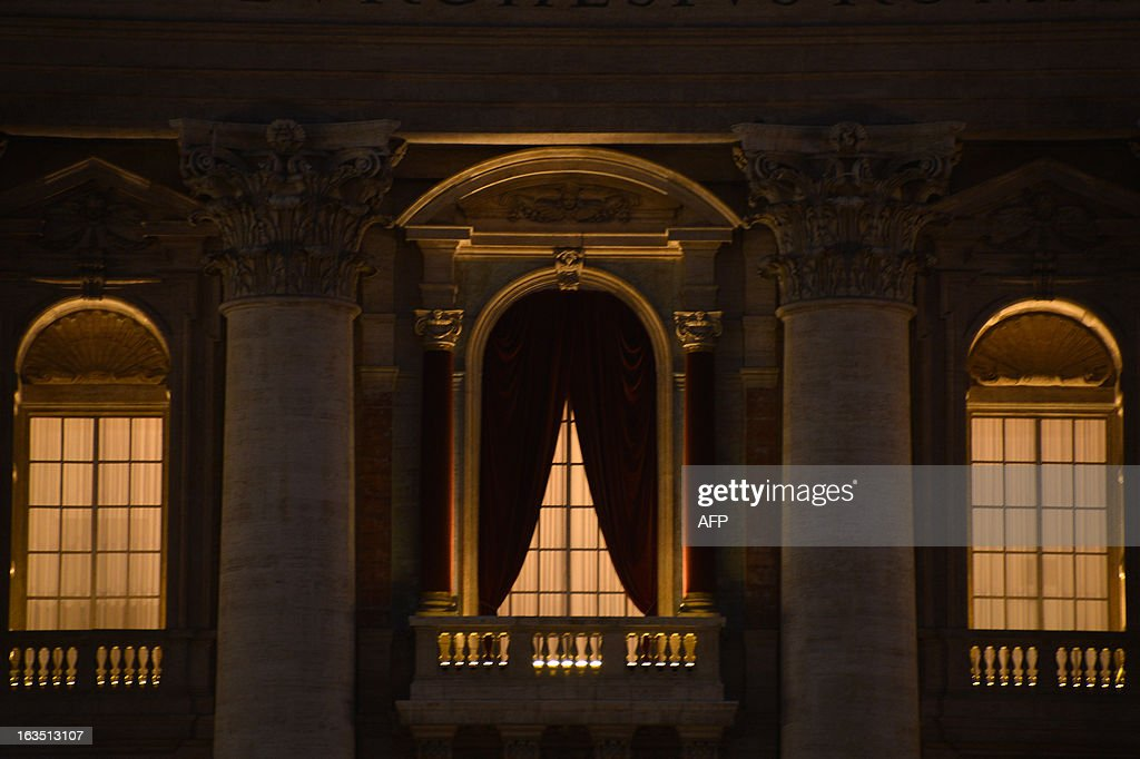 A picture shows the curtains hanged on the central balcony of St Peter's basilica at night on the eve of the conclave on March 11, 2013 at the Vatican. Catholic cardinals had a final day of jockeying for position the same day before shutting themselves into the Sistine Chapel to elect a new pope after Benedict XVI's shock resignation, with an Italian and a Brazilian who both head powerful archdioceses among the top contenders. AFP PHOTO / GABRIEL BOUYS