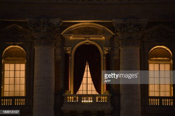 A picture shows the curtains hanged on the central balcony of St Peter's basilica at night on the eve of the conclave on March 11 2013 at the Vatican...