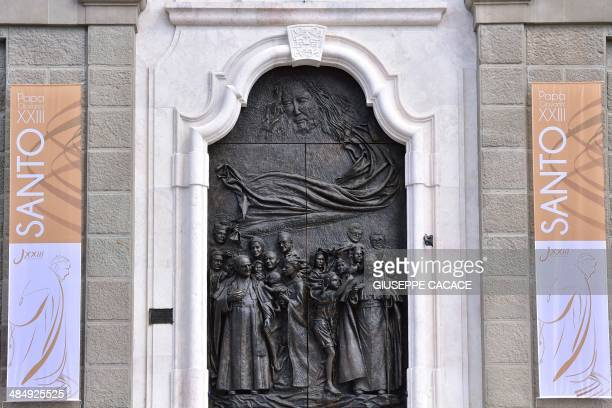 A picture shows the door of Saint John church depicting late popes John XXIII and John Paul II in Sotto il Monte Giovanni XXIII on April 15 2014...