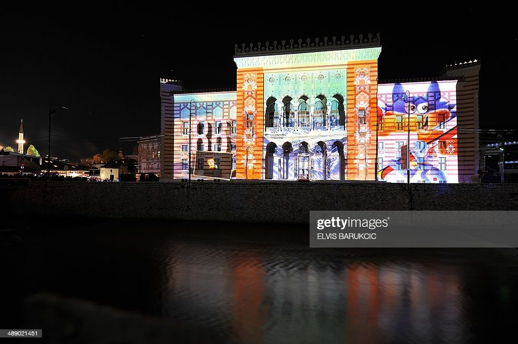 A picture shows the facade of Sarajevo City Hall and National Library building lit with 3D mapping animations depicting the 1984 Winter Olympic Games mascot and logo during a grand re-opening ceremony, on May 9, 2014. Sarajevo City Hall was built in 1896 while Bosnia was under Austro-Hungarian rule (1878-1914) and was re-purposed into National Library after World War II. It used to contain more than 2 millions of books and artifacts before it was destroyed in a fire caused by mortar and artillery shells fired from Bosnian Serb postions overlooking the city, in the night between August 25-26, 1992. Only some 300.000 pieces of the material were saved from the flames. The building was under reconstruction, mostly founded by the EU, since 1996. AFP / PHOTO ELVIS BARUKCIC