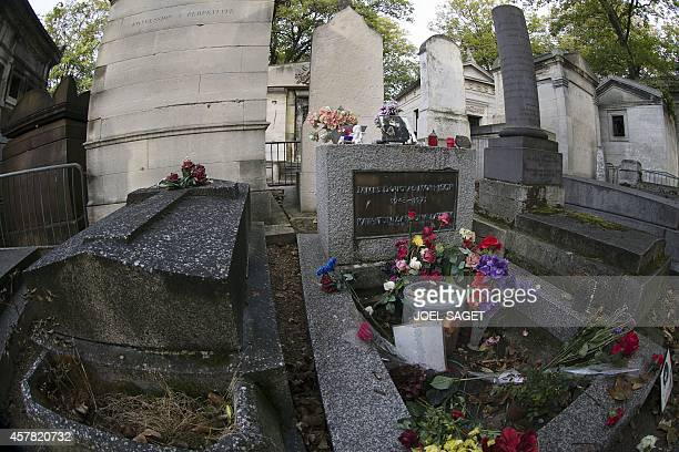 MALSANG A picture shows the grave of US singer Jim Morrison at the PereLachaise cemetery in Paris on October 16 2014 in Paris From flowers and...