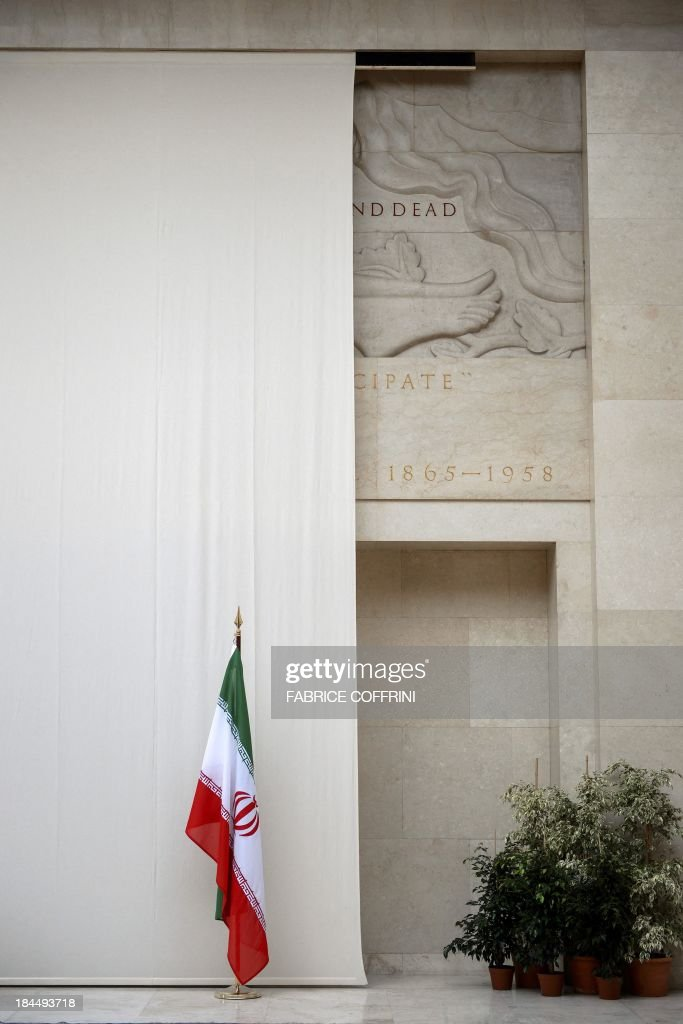 A picture shows the Iranian flag in front of a sculpture of a naked man covered up by a curtain on October 14, 2013 at the United Nations' Geneva offices, ahead of fresh talks between world powers and Iran on its controversial nuclear programme. The cover-up of the marble man and his clearly visible penis was first reported by the Swiss newspaper Tribune de Geneve, which claimed that the aim was to avoid offending the Islamic republic's delegation talks. Swiss officials declined to address the newspaper's claim, and told AFP that the aim was to provide a neutral backdrop at the entrance to the meeting hall.