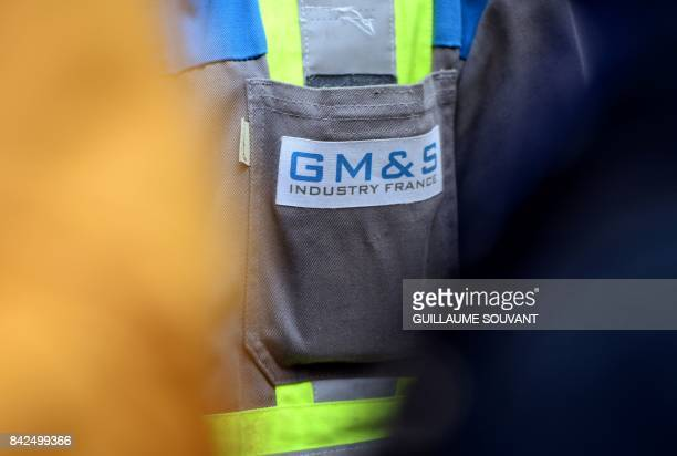 A picture shows the logo of French auto parts manufacturer GMS on an employees' clothes outside the trade court of Poitiers central France on...