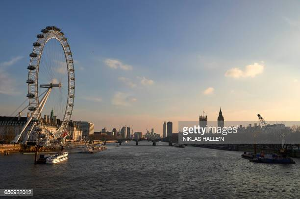 A picture shows the London Eye Westminster Bridge over the River Thames and the Houses of Parliament in central London on March 23 2017 a day after...