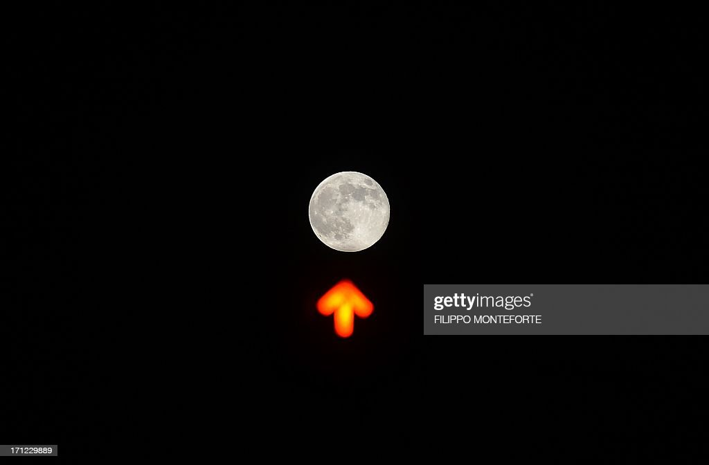 A picture shows the moon over a traffic light in downtown Rome on June 23, 2013. The full moon at perigee, called a 'supermoon' ,is the largest and closest full moon of the year as it appears 14 percent larger and 30 per cent brighter than normal as Earth's satellite orbits within about 357,000 kilometers of our planet. AFP PHOTO / Filippo MONTEFORTE