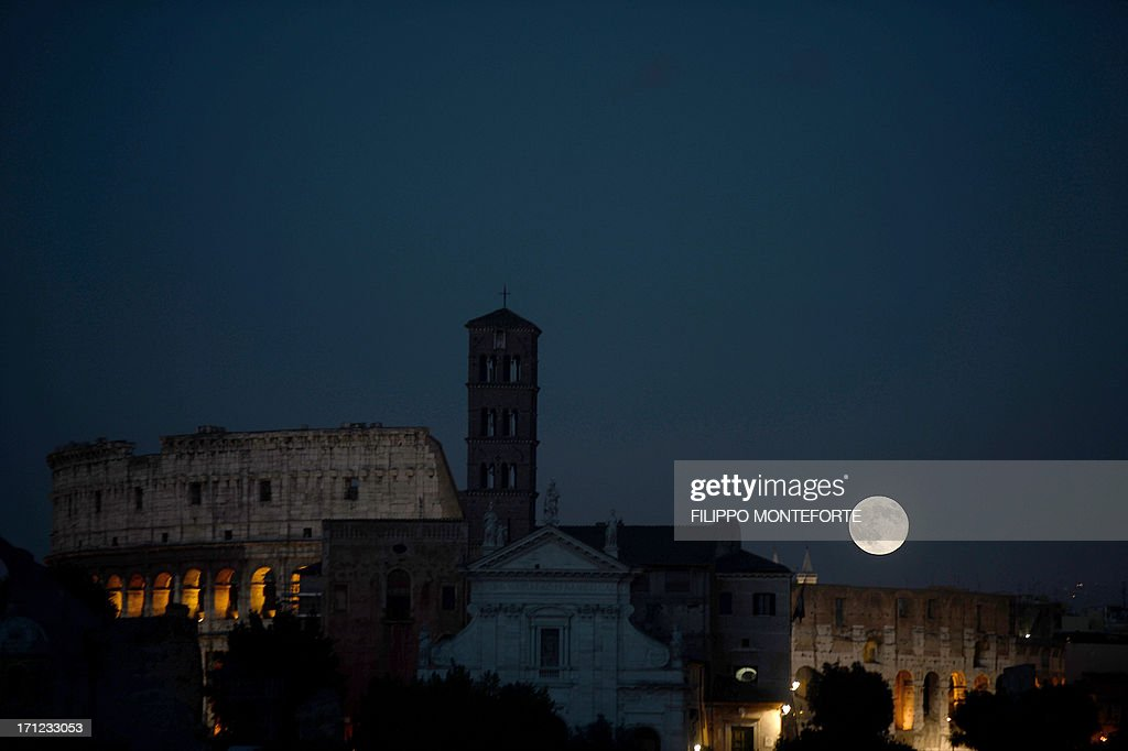 A picture shows the moon over the Colosseum and the Roman Forum in downtown Rome on June 23, 2013. The full moon at perigee, called a 'supermoon' ,is the largest and closest full moon of the year as it appears 14 percent larger and 30 per cent brighter than normal as Earth's satellite orbits within about 357,000 kilometers of our planet. AFP PHOTO / Filippo MONTEFORTE