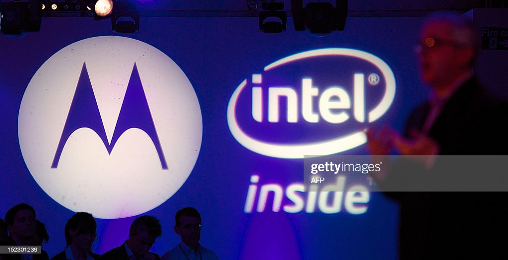 A picture shows the Motorola and Intel branding logos as general manager for Intel Mobile and Communications Group, Erik Reid (R), talks during the press launch of the new Motorola RAZRi smartphone with an Intel processor in London on September 18, 2012. Motorola Mobility presented their new smartphone, developed with an Intel processor powering its Android operating system, which will be launched in October in Europe and Latin America with the hope that it will compete with the Apple iPhone. AFP PHOTO / ANDREW COWIE