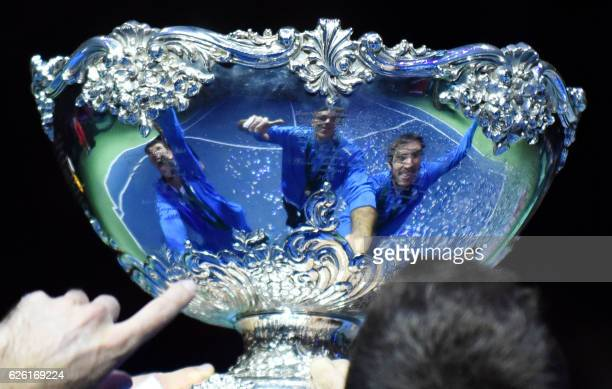TOPSHOT A picture shows the reflections of Argetina's Federico Delbonis Juan martin del Potro and Leonardo Mayer on the trophy during celebrations...