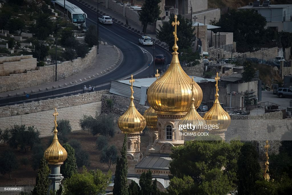 A picture shows the Russian Orthodox Church of Mary Magdalene situated at Mount of Olives in east Jerusalem on June 28, 2016. The church was built in 1886 by Tsar Alexander III to honor his mother, Empress Maria Alexandrovna of Russia. It was constructed to David Grimm's design in the traditional tented roof style popular in 16th- and 17th-century Russia, and includes seven distinctive, gilded onion domes. / AFP / THOMAS