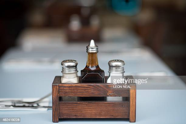 A picture shows the salt pepper and vinegar on a table at Poppies fish and chip restaurant in east London on January 26 2015 Fish and chips that a...