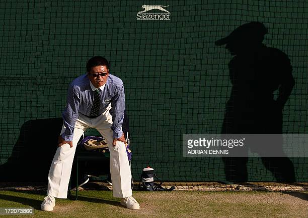 A picture shows the shadow of a ballboy as he looks toward a line judge as Czech Republic's Tomas Berdych plays against Australia's Bernard Tomic...