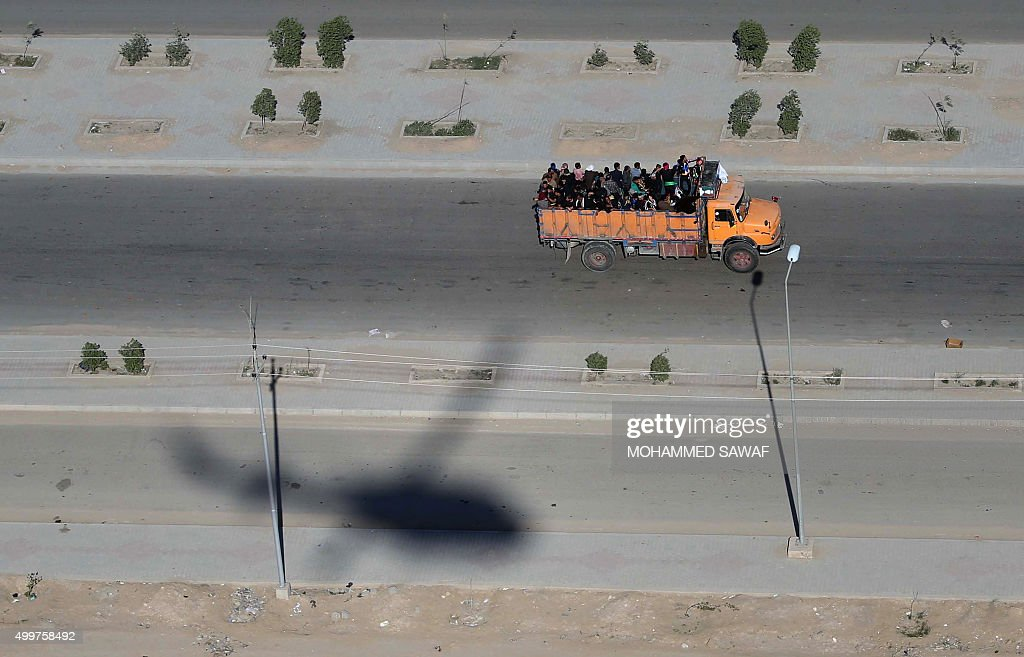 TOPSHOT A picture shows the shadow of an Iraqi security forces helicopter while a truck transports Shiite Muslim pilgrims on December 3 2015 in the...