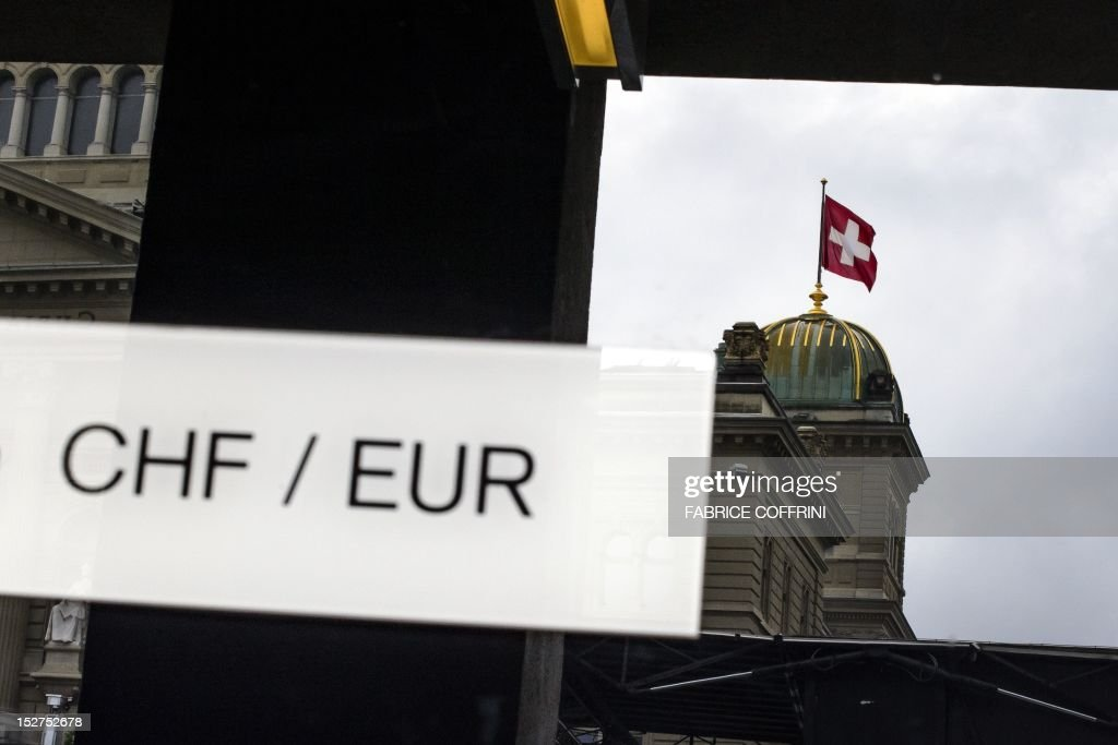 A picture shows the signs of Swiss Francs (CHF) and Euro (EUR) in front of the reflection of the Swiss flag on top of the Swiss Parliament building September 22, 2012 in Bern. The Swiss central bank (SNB) is shoring up the eurozone's government bond market and holding down the interest rates which five key countries pay to borrow, ratings agency Standard & Poor's estimated on September 25, 2012. AFP PHOTO / FABRICE COFFRINI