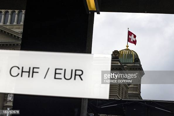 A picture shows the signs of Swiss Francs and Euro in front of the reflection of the Swiss flag on top of the Swiss Parliament building September 22...