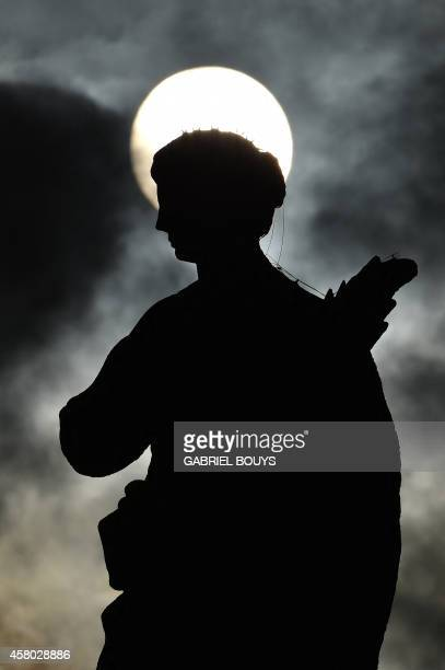 A picture shows the silhouette of a statue at St Peter's square as the sun rises through clouds before a general audience of pope Francis on October...