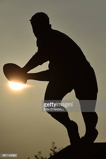 A picture shows the silhouette of a statue of a rugby player outside Twickenham stadium south west London prior to a Pool A match of the 2015 Rugby...