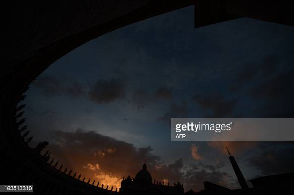 A picture shows the St Peter's basilica and the Colonnade at sunset on the eve of the conclave on March 11 2013 at the Vatican Catholic cardinals had...