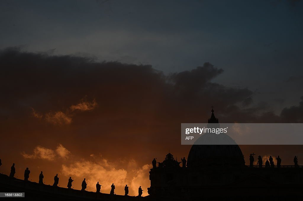 A picture shows the St Peter's basilica at sunset on the eve of the conclave on March 11, 2013 at the Vatican. Catholic cardinals had a final day of jockeying for position the same day before shutting themselves into the Sistine Chapel to elect a new pope after Benedict XVI's shock resignation, with an Italian and a Brazilian who both head powerful archdioceses among the top contenders. AFP PHOTO / FILIPPO MONTEFORTE