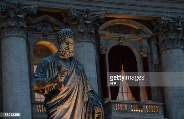 A picture shows the St Peter's statue in front of the main window of the St Peter's basilica on the eve of the conclave on March 11 2013 at the...