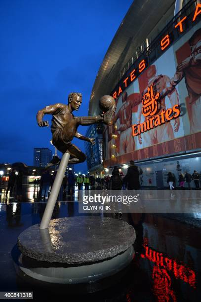 A picture shows the statue of Arsenal's Dutch former player Dennis Bergkamp outside the stadium ahead of the English Premier League football match...