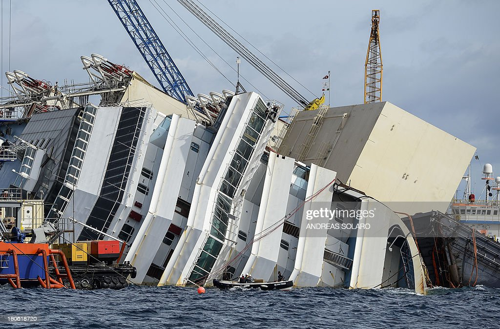 A picture shows the wreck of Italy's Costa Concordia cruise ship near the harbour of Giglio Porto on September 15, 2013. Salvage workers will attempt to raise the cruise ship on September 16, 2013, weather permitting, in the largest and most expensive maritime salvage operation in history, so-called 'parbuckling', to rotated the ship by a series of cables and hydraulic machines. Thirty-two people died when the ship, with 4,200 passengers onboard, hit rocks and ran aground off the island of Giglio on January 2012.