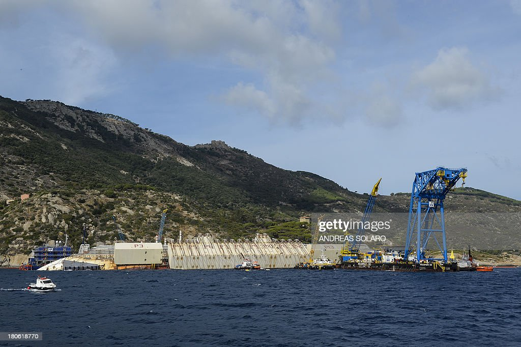 A picture shows the wreck of Italy's Costa Concordia cruise ship near the harbour of Giglio Porto on September 15, 2013. Salvage workers will attempt to raise the cruise ship on September 16, 2013, weather permitting, in the largest and most expensive maritime salvage operation in history, so-called 'parbuckling', to rotated the ship by a series of cables and hydraulic machines. Thirty-two people died when the ship, with 4,200 passengers onboard, hit rocks and ran aground off the island of Giglio on January 2012. AFP PHOTO / ANDREAS SOLARO