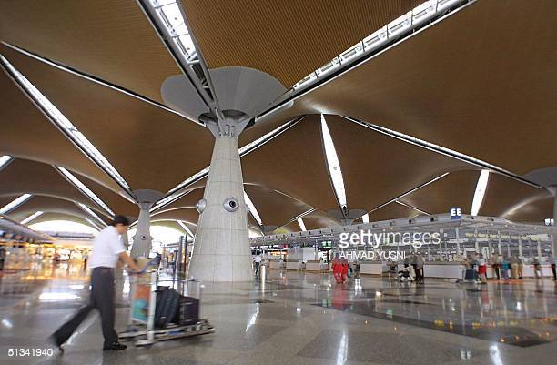 Picture taken 11 May 2002 shows a man pushing a trolley at Kuala Lumpur International Airport in Sepang south of Kuala Lumpur Singapore has won a...