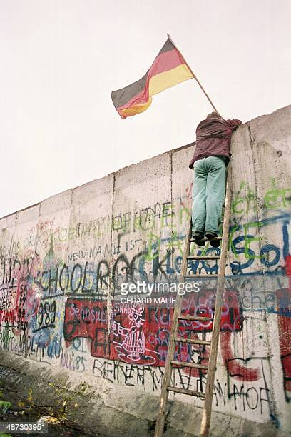 A picture taken 11 November 1989 shows a West Berliner preparing to hand over a FRG flag to East German Vopo policemen through a portion of the...