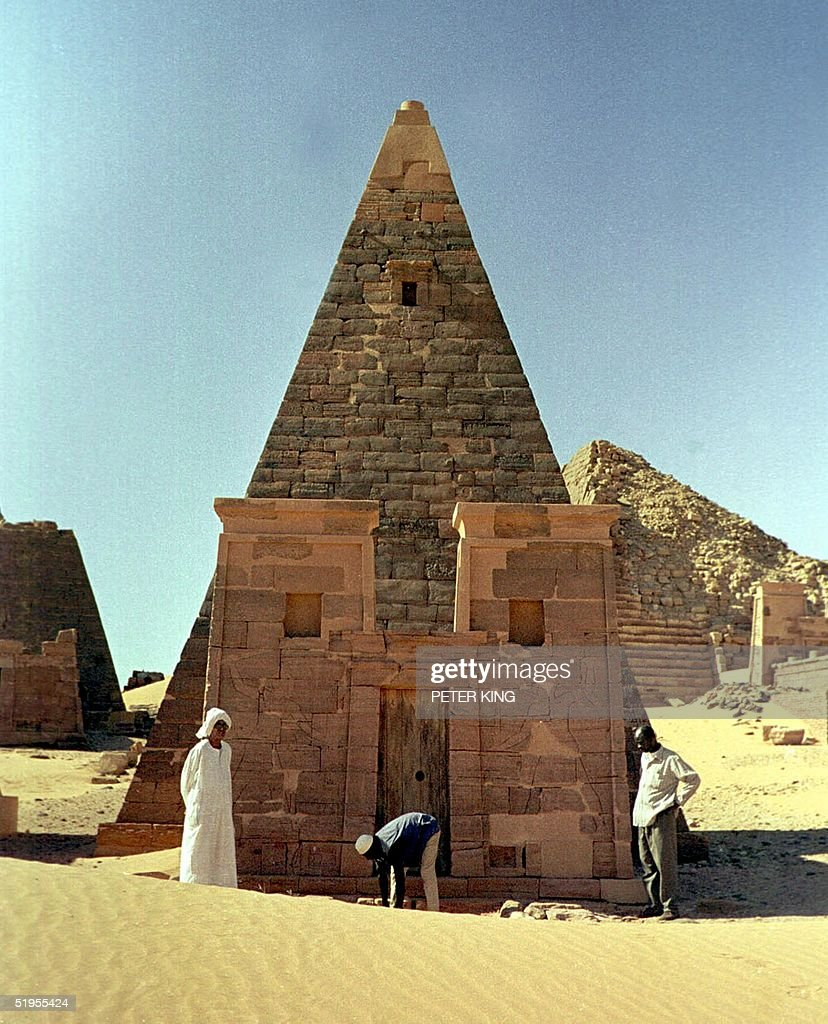 Picture taken 16 December 2000 shows Sudanese workers in front of the Royal Pyramids of Meroe in Sudan's northern desert, some 300 kms north of Khartoum. These distant relatives of Egypt's Great Pyramids are 2,000-year-old royal tombs with the larger pyramids devoted to the kings and the smaller ones to the nobles of Meroe who ruled Sudan from 592 BC to 350 AD. Two Italian tour operators are now running trips to Meroe and a luxury campsite was opened near the remains in November 2000.