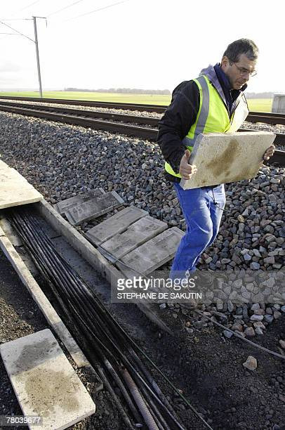 A picture taken 21 November 2007 in Varredes eastern Paris shows a cable worker walking past damaged cable arteries on East line of highspeed TGV...