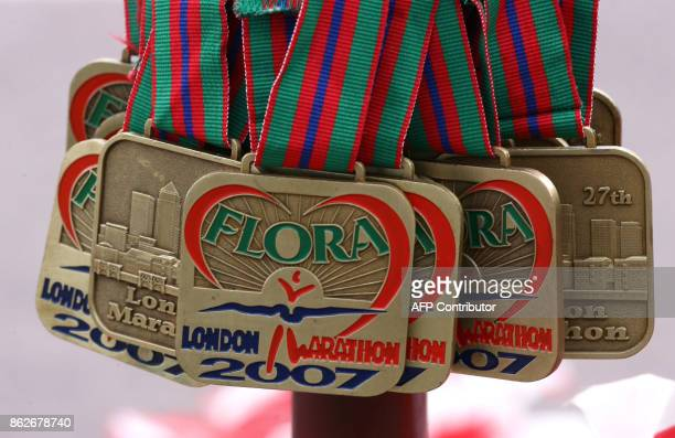 Picture taken 22 April 207 shows the medals awarded to those who completed the London Marathon hanging on a post near the finish line Kenyan Martin...