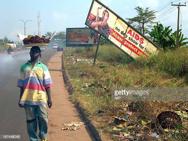 A picture taken 28 November 2005 shows a street food seller walking past by a roten signpost showing Nigerian popular singer Femi Kuti campaigning to...