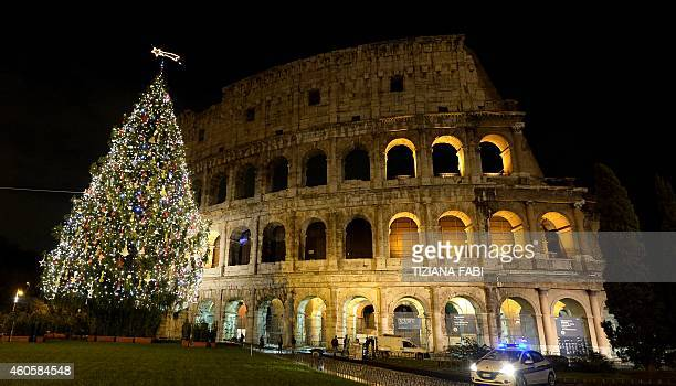 A picture taken at night shows lights on a Christmas tree and the Colosseum in the background on December 16 2014 in Rome AFP PHOTO / TIZIANA FABI