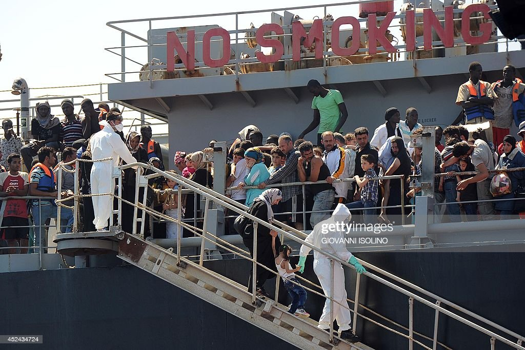 A picture taken at sea shows the transfer of immigrants from the tanker 'Torm Lotte' to tug boat 'Grifone' in the middle of Messina's marine channel...
