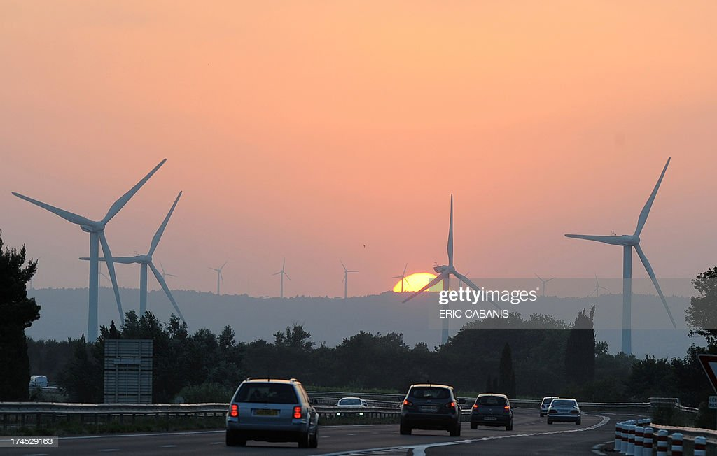 A picture taken at sunset on July 26, 2013 shows wind turbines at the background and vehicles driving along the highway between Narbonne and Toulouse in Bram, southwestern France, during a weekend traditionally marked by heavy traffic for the summer holiday departures. AFP PHOTO / ERIC CABANIS