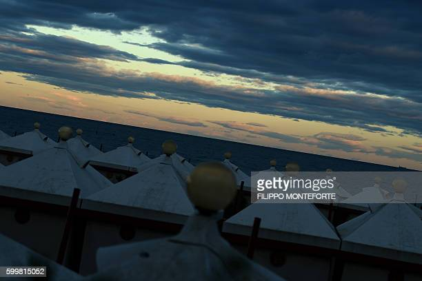 A picture taken at sunset shows cabins on the beach during the 73rd Venice Film Festival on September 6 2016 at Venice Lido / AFP / FILIPPO MONTEFORTE
