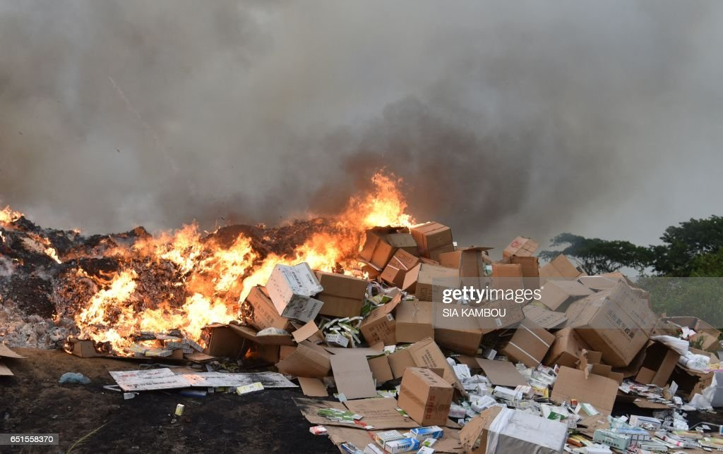 A picture taken at the cemetery of Abobo district of Abidjan on March 10, 2017 shows fake medecine being incinerated. 50 tonnes of fake medicine, for an estimated value of more than 1 million euros, were burnt in Abidjan on March 10, 2017. / AFP PHOTO / Sia KAMBOU