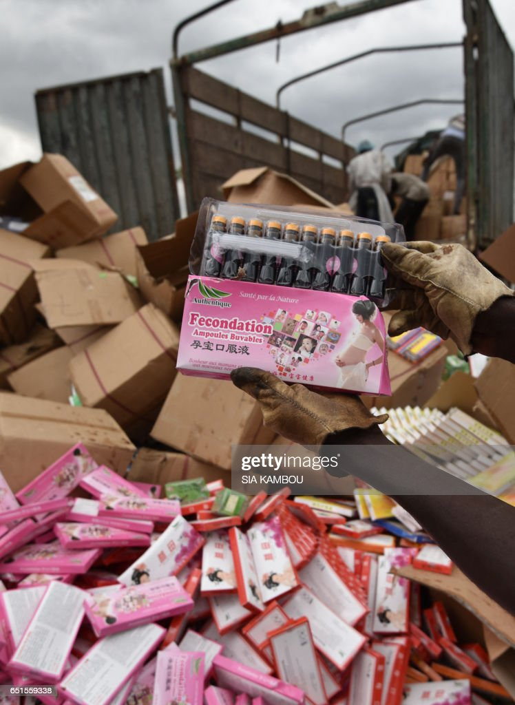 A picture taken at the cemetery of Abobo district of Abidjan on March 10, 2017 shows fake medecine bearing Chinese character as people unload boxes of counterfeit drugs from a truck. 50 tonnes of fake medicine, for an estimated value of more than 1 million euros, were burnt in Abidjan on March 10, 2017. / AFP PHOTO / Sia KAMBOU