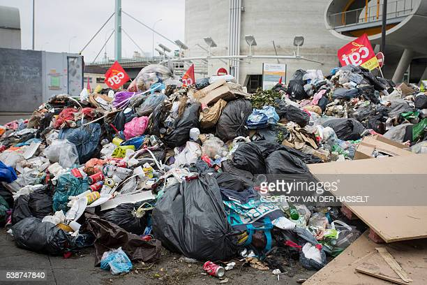 A picture taken at the entrance of a waste treatment site blocked by strikers in IvrysurSeine near Paris on June 8 2016 shows a rubbish pile next to...